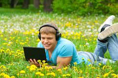 Young man using a laptop and listening music Royalty Free Stock Image
