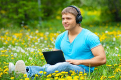 Young man using a laptop and listening music Stock Photos