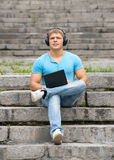Young man using a laptop and listening music Royalty Free Stock Images