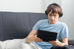 Young man using a laptop and listening music Stock Image