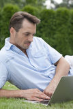Young man using laptop while lying on grass in park Stock Image
