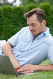Young man using laptop while lying on grass in park Royalty Free Stock Image