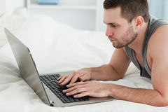 Young man using a laptop while lying on his belly Stock Photography