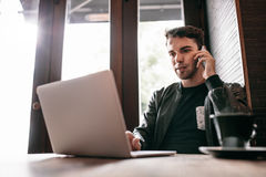 Young man using laptop and mobile phone at cafe Royalty Free Stock Photo