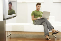 Young Man Using Laptop In Modern Apartment Stock Image
