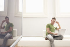 Young Man Using Laptop In Modern Apartment Royalty Free Stock Image