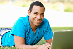 Young man using laptop outdoors. Smiling at camera stock image