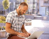 Young man using laptop outdoors. Young man sitting outdoors, using laptop at summertime stock images