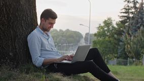 A Young Man Using a Laptop Outdoors. A young man using a laptop and sitting under the tree. Long shot. Soft focus stock video footage
