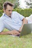 Young man using laptop in park Stock Photos