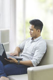 young man using laptop pc while sitting on a couch at home Royalty Free Stock Images