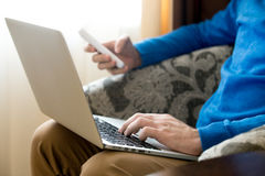 Young man using laptop and phone Stock Image