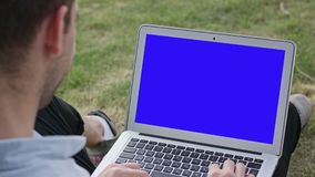 A Young Man Using a Laptop Outdoors. A young man using a laptop and sitting on the grass. Blue screen. Closeup shot. Soft focus Royalty Free Stock Image