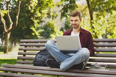Young man using laptop sitting outdoors. Happy smiling man using laptop sitting outdoors and typing on the computer with his legs crossed under him. Technology Stock Photos