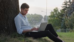 A Young Man Using a Laptop Outdoors. A young man using a laptop and sitting under the tree. Long shot. Soft focus stock footage