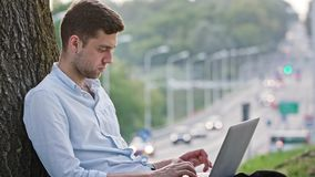 A Young Man Using a Laptop Outdoors. A young man using a laptop and sitting under the tree. Medium shot. Soft focus stock footage