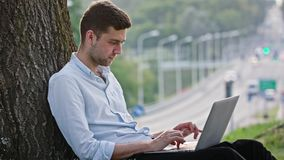 A Young Man Using a Laptop Outdoors. A young man using a laptop and sitting under the tree. Medium shot. Soft focus stock video footage