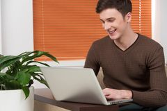 Young man using laptop and smiling. Royalty Free Stock Photo