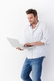 Young man using laptop standing smiling Royalty Free Stock Photo