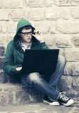 Young man using laptop on the steps. Young fashion man using laptop on the steps Stock Photography
