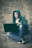Young man using laptop on the steps. Young man in a hood using laptop on the steps Royalty Free Stock Images