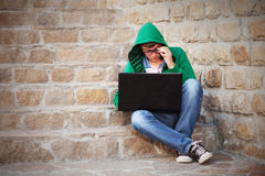 Young man using laptop on the steps. Young man in a hoodie using laptop on the steps Royalty Free Stock Photography