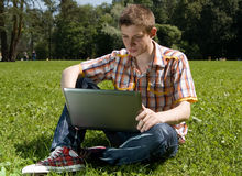 Young man using laptop in summer park Stock Image