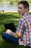 Young man using laptop in summer park Stock Photography