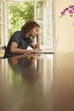 Young Man Using Laptop At Table Royalty Free Stock Image