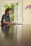 Young Man Using Laptop At Table Stock Images