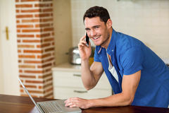 Young man using laptop and talking on phone Royalty Free Stock Image