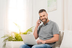 Young man using laptop and talking on smartphone while sitting on sofa and smiling at camera Royalty Free Stock Photography