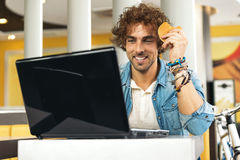Young man using laptop while to have lunch. Stock Images