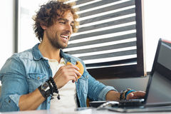 Young man using laptop while to have lunch. Stock Photography