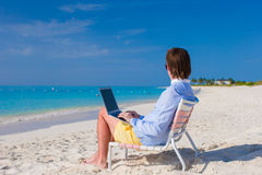 Young man using laptop on tropical beach Stock Images