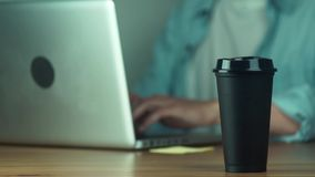 Young man using laptop typing message. Man takes a black hot mug. From the table with coffee stock footage