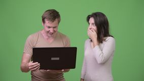 Young man using laptop with young woman looking shocked. Studio shot of young handsome Scandinavian man and young beautiful woman together against chroma key stock footage