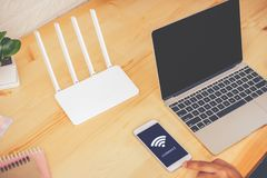 Young man using mobile with connect wifi on the screen. Man`s hands using device at Home office. Blurred background stock photo