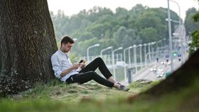 A Young Man Using a Mobile Outdoors. A young man using a mobile and having a snack outdoors. Long shot. Soft focus Royalty Free Stock Photo