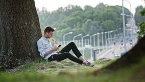 A Young Man Using a Mobile Outdoors. A young man using a mobile and having a snack outdoors. Long shot. Soft focus Stock Photos