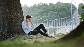 A Young Man Using a Mobile Outdoors. A young man using a mobile and sitting under the tree. Long shot. Soft focus Royalty Free Stock Photography