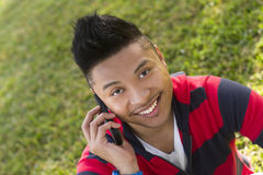 Young man using a mobile phone. A good looking, happy young man using a mobile phone outdoors Stock Photos