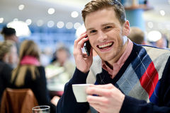 Young man using mobile phone in cafe Royalty Free Stock Photos