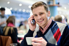 Young man using mobile phone in cafe Royalty Free Stock Photo
