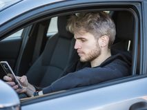 Young Man using mobile phone while driving. Handsome Young Man using mobile phone while driving a car Stock Images