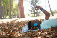 Young man using mobile phone while lying on a picnic blanket Stock Photos