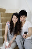 Young man using mobile phone photographing self with young woman Stock Photo