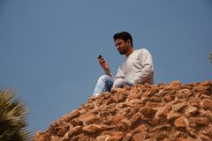 Young man using mobile phone sitting on a high wall. A young man using his mobile phone sitting on a high bricks wall isolated unique royalty free image stock image