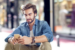 Young man using mobile phone in street Stock Photo