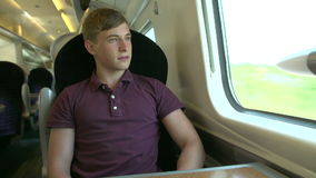 Young Man Using Mobile Phone On Train Journey